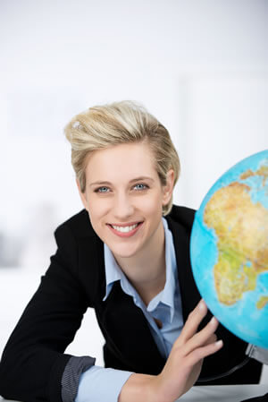 Businesswoman posing next to a globe