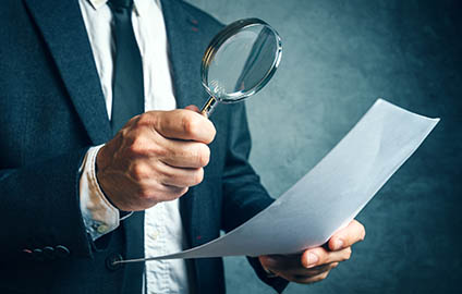 Businessman using a magnifying glass to review a document.