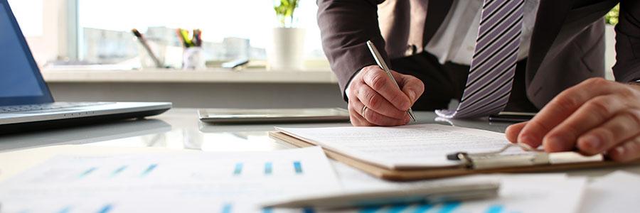 Businessman writing on a clipboard
