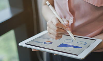 A businesswoman using a tablet and smart stylus to review her business dashboard.