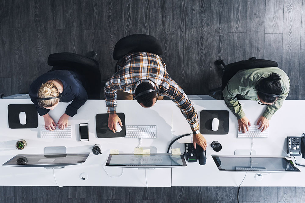 Overhead shot of three technology consultants working at a long desk.