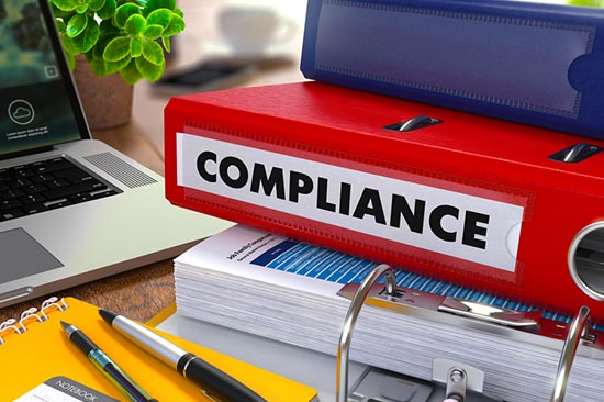 """Red binder labeled """"Compliance"""""""