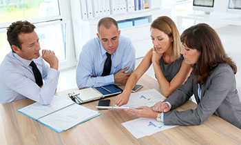 4 people in a business meeting reviewing financial documents