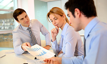 3 business people in a meeting reviewing a financial document