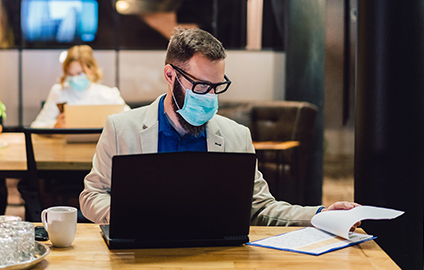 Businessman wearing a mask while working at his desk