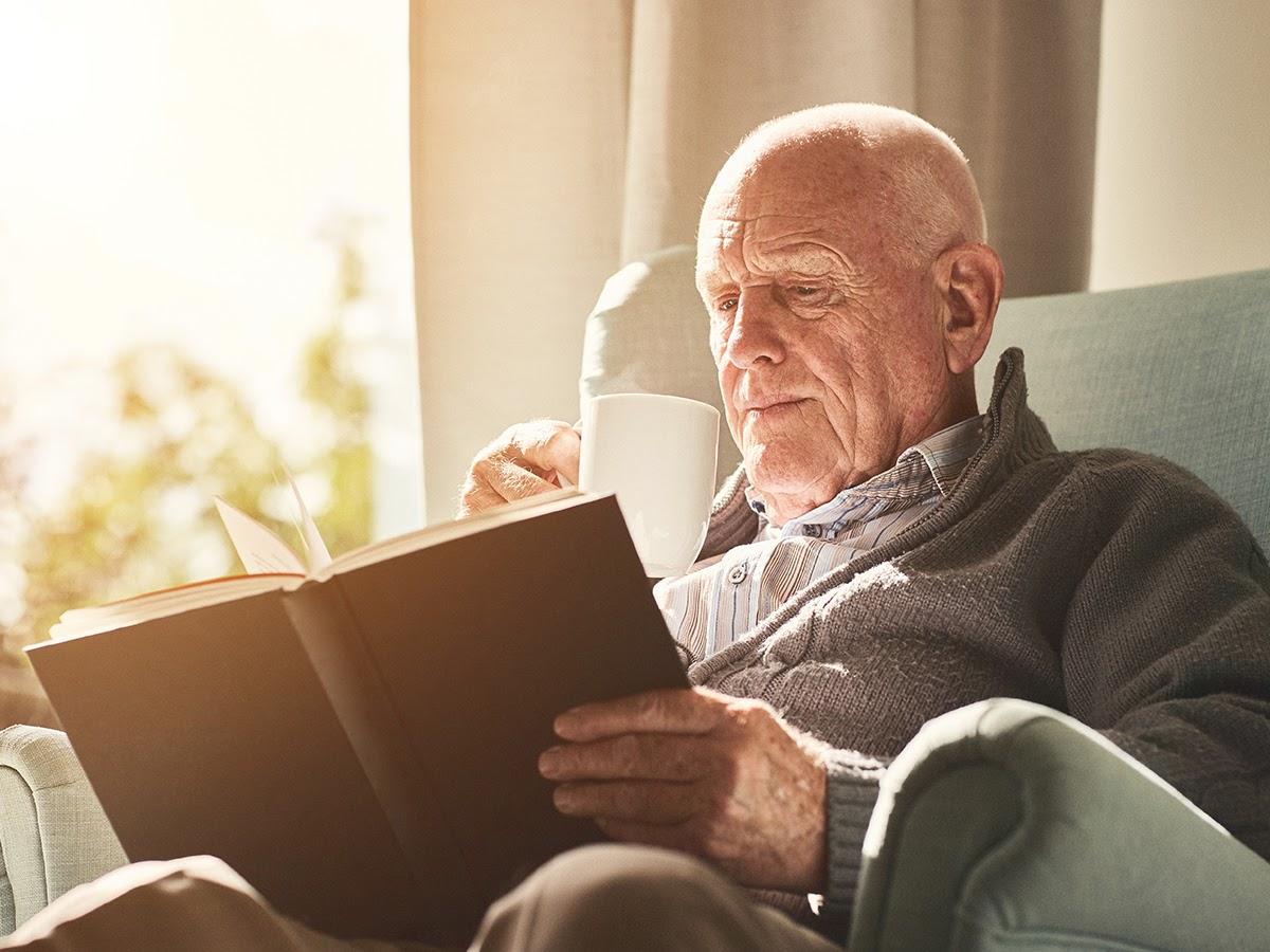 An elderly man sits in an armchair reading a book