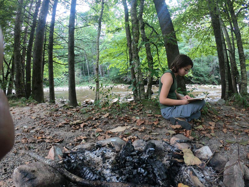 Image of teen girl reading her book under a tree next to a fire pit along the South Toe River while camping at Black Mountain Campground in Pisgah National Forest, North Carolina