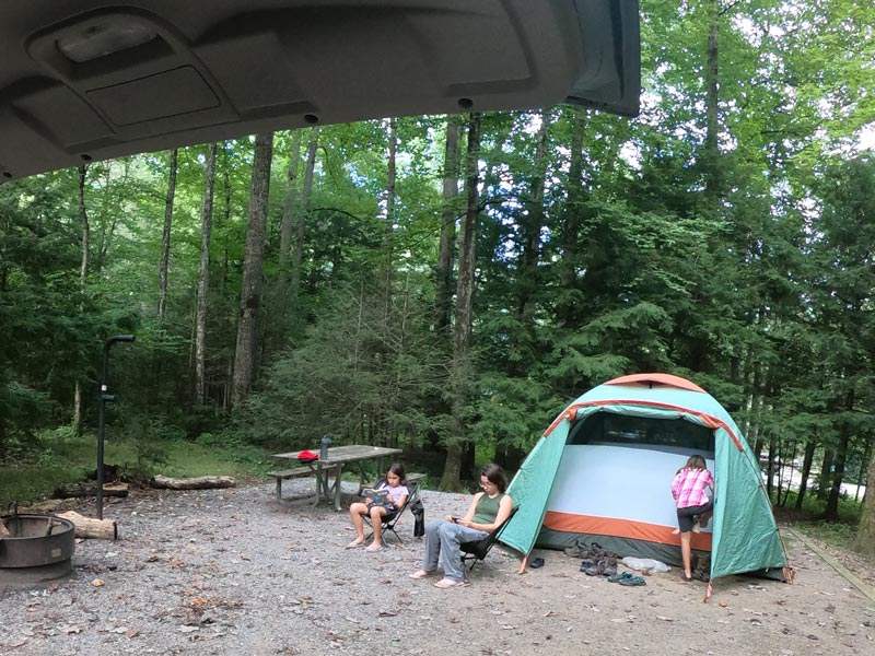 Image of Black Mountain Campground campsite with two girls relaxing in chairs while one girl enters the tent near Blue Ridge Parkway in North Carolina