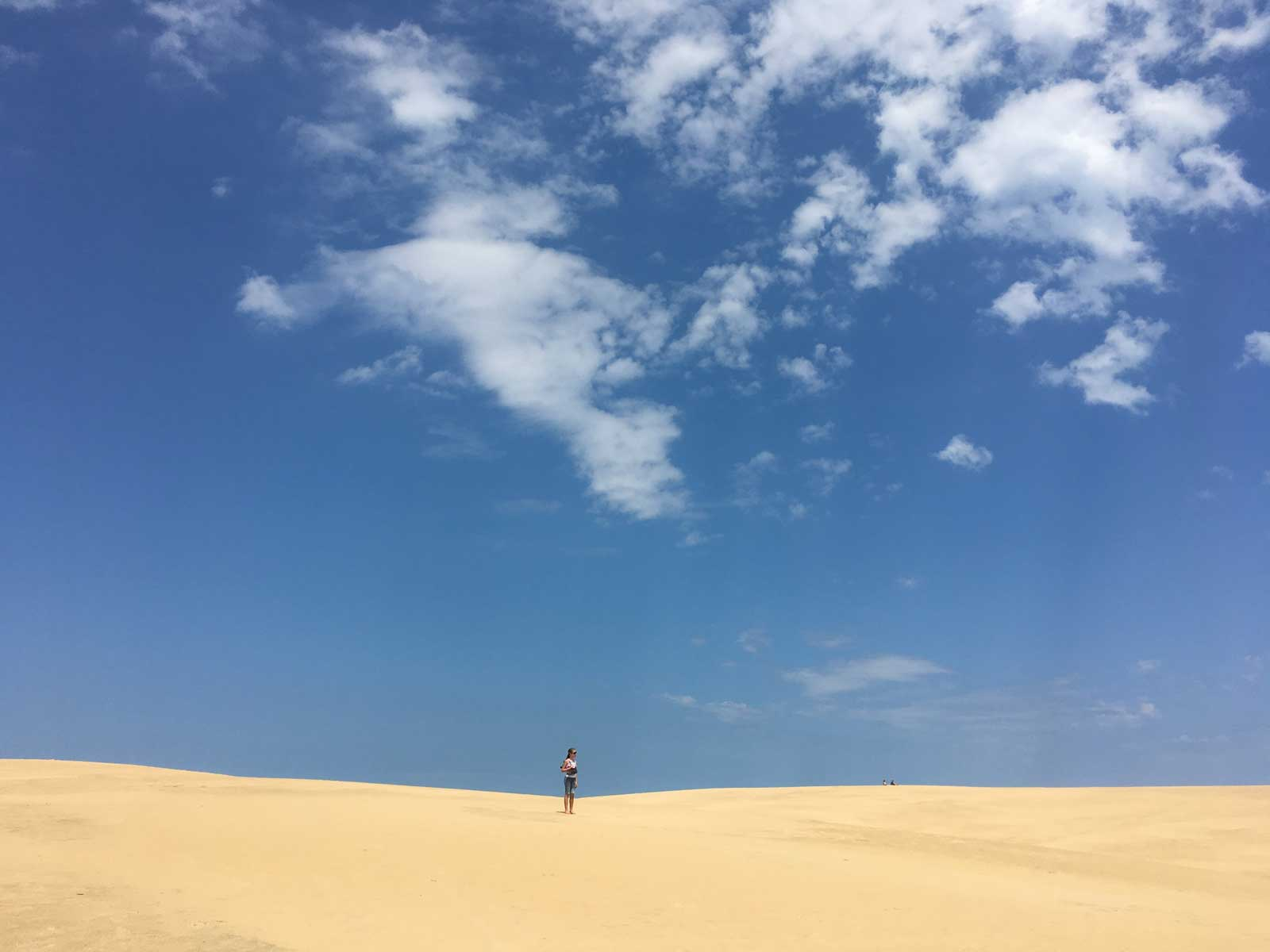 A girl on top of Jockeys Ridge on the Outer Banks of North Carolina near Nags Head and Cape Hatteras.