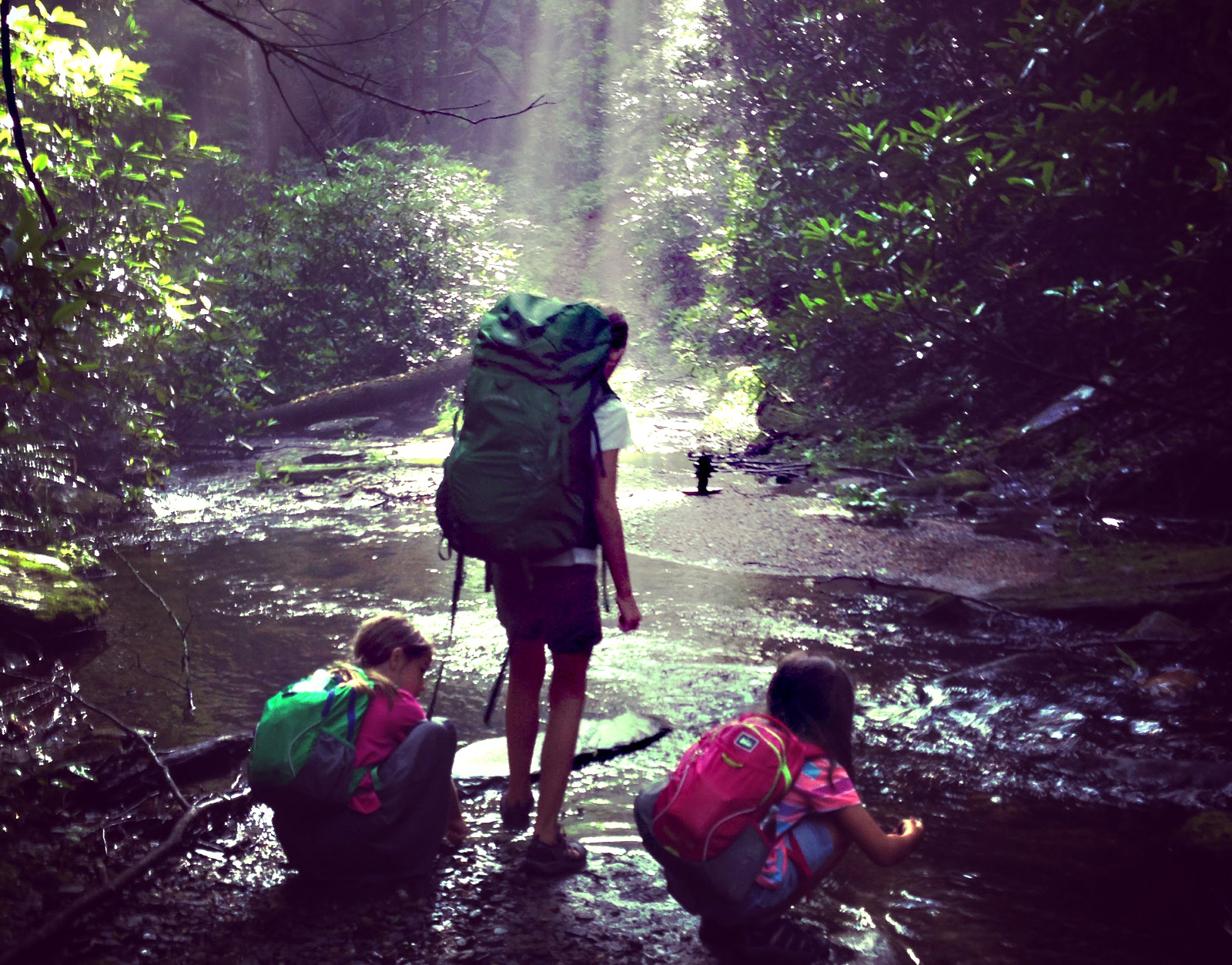 Photo of three girls backpacking on the Widow's Creek trail at Stone Mountain State Park in North Carolina