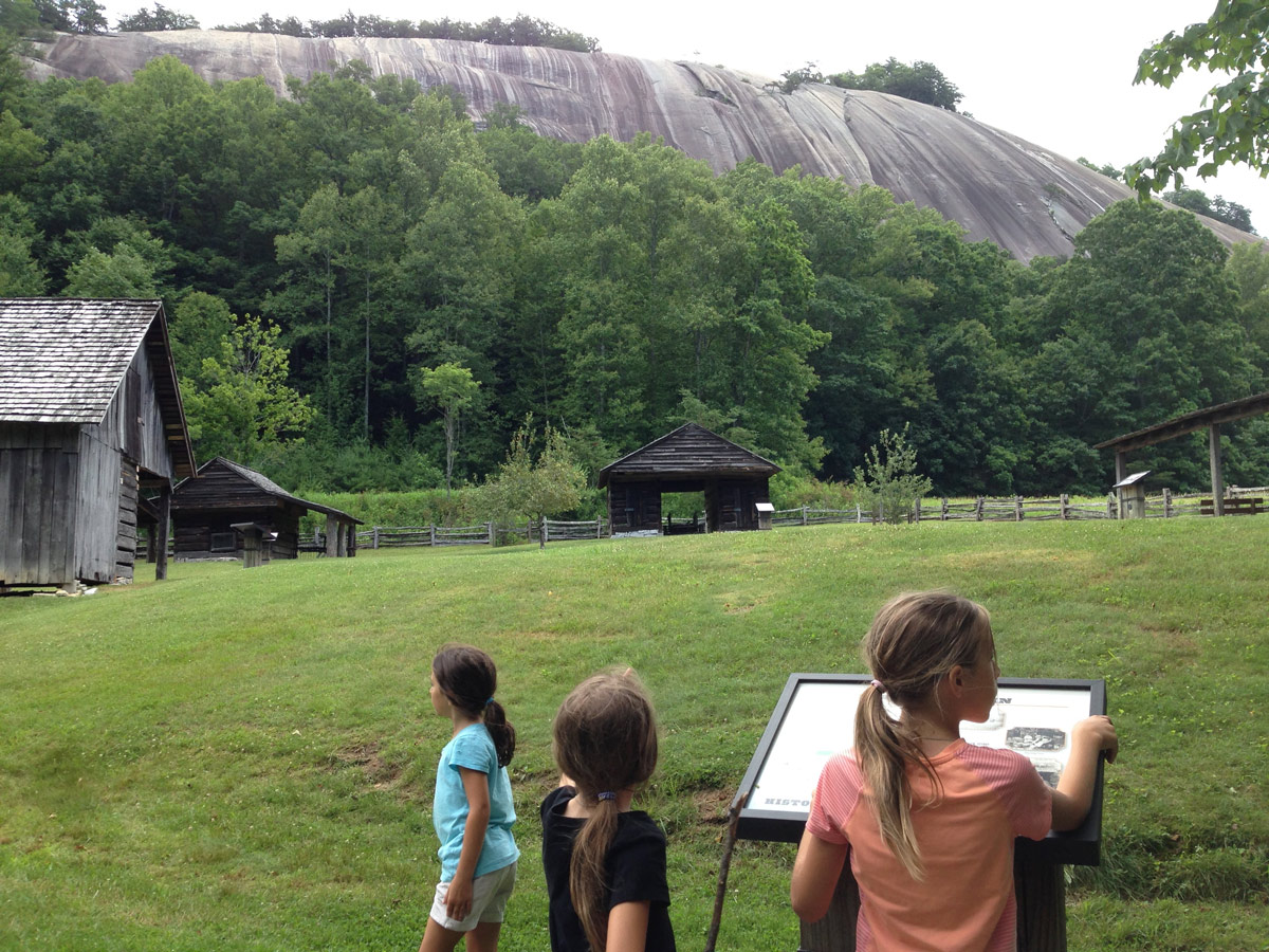 Photograph of three girls looking at the granite Stone Mountain and the restored 19th century farm, Hutchison Homestead, in Stone Mountain State Park, North Carolina