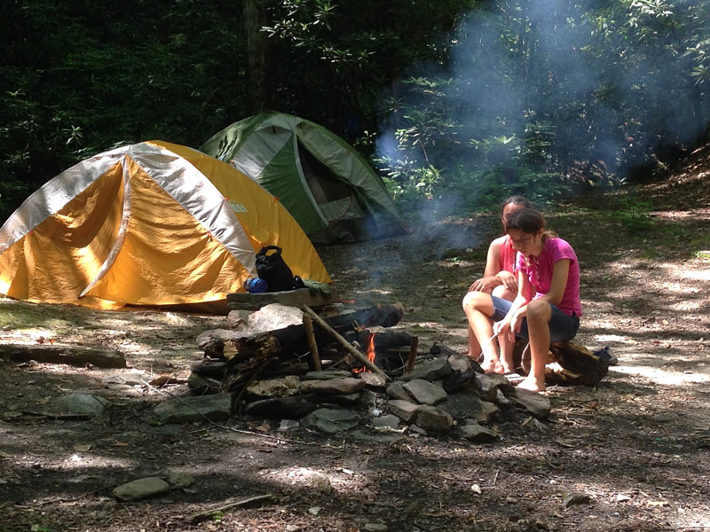 Image of two girls sitting by their campfire with two REI tents, one orange and one green, in the background of Stone Mountain State Park, North Carolina