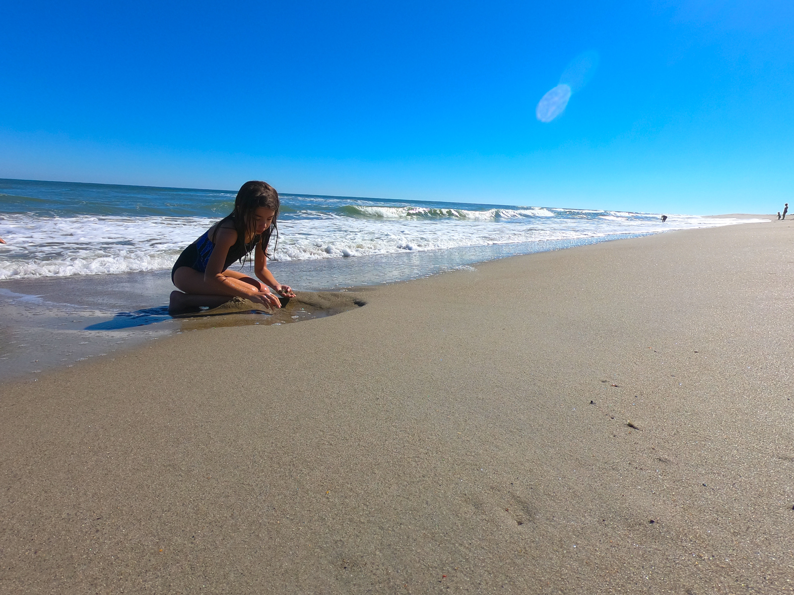 Girl playing in the surf under a blue sky at Carolina Beach in North Carolina
