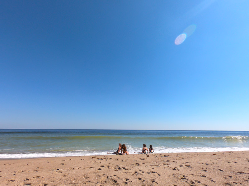 Photo of four sisters sitting in the surf on a gorgeous sunny day under a brilliant blue October Sky on Kure Beach, North Carolina