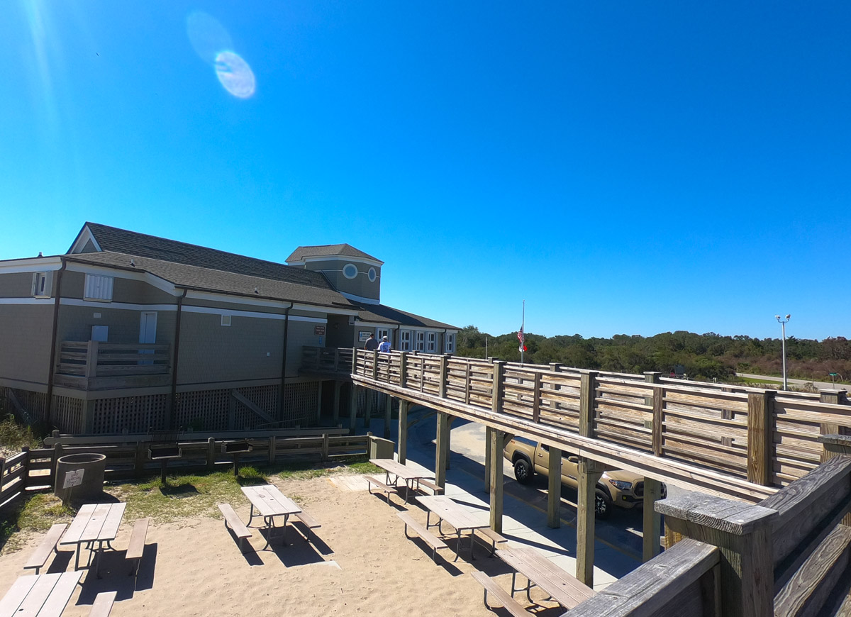 Photo of Fort FIsher Recreation area visitor center, boardwalk, and picnic tables under an azure sky at Kure Beach, North Carolina