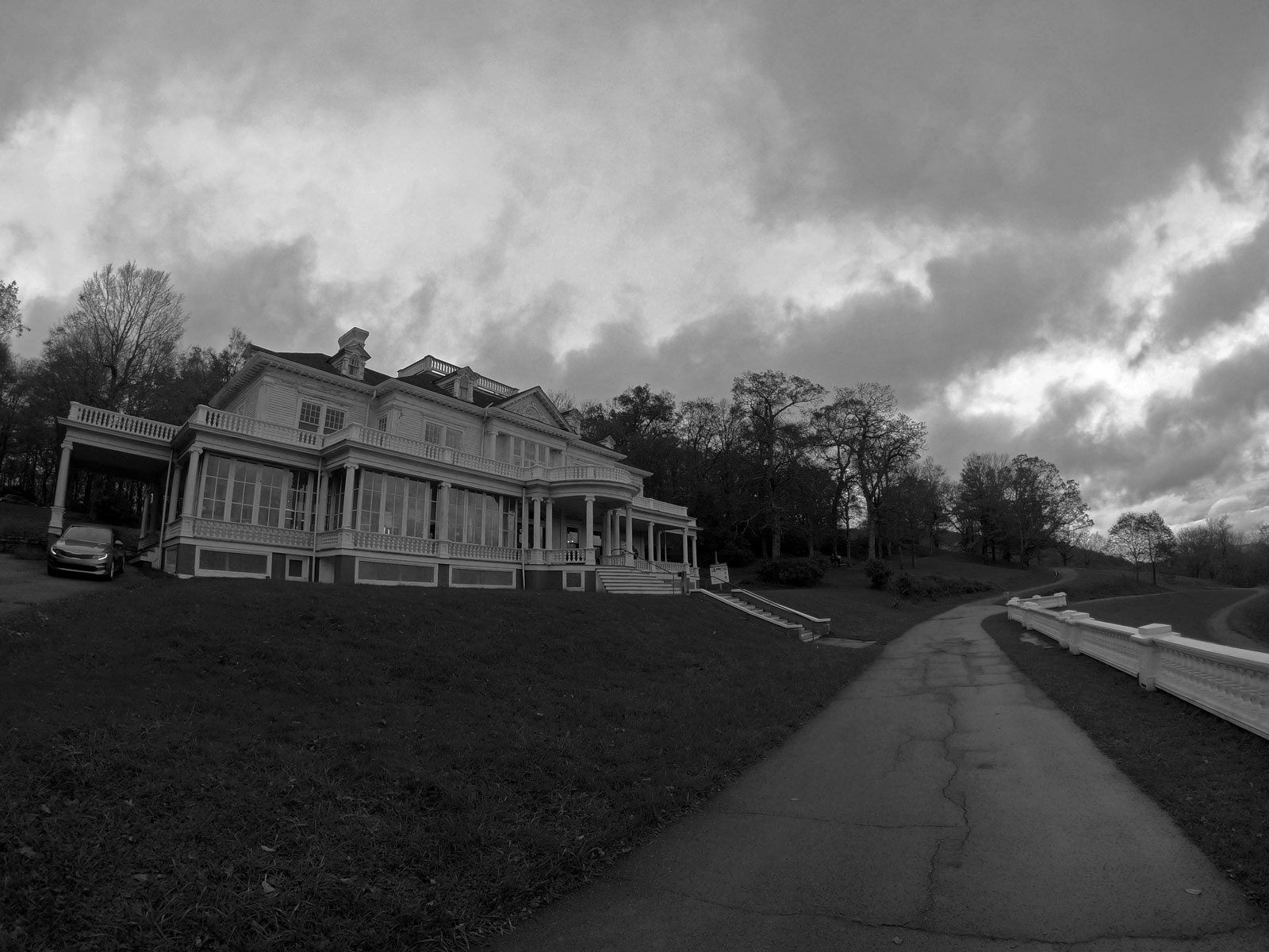 Dramatic black and white image of Moses Cone Memoria Park and Flat Top Manor mansion on a hill