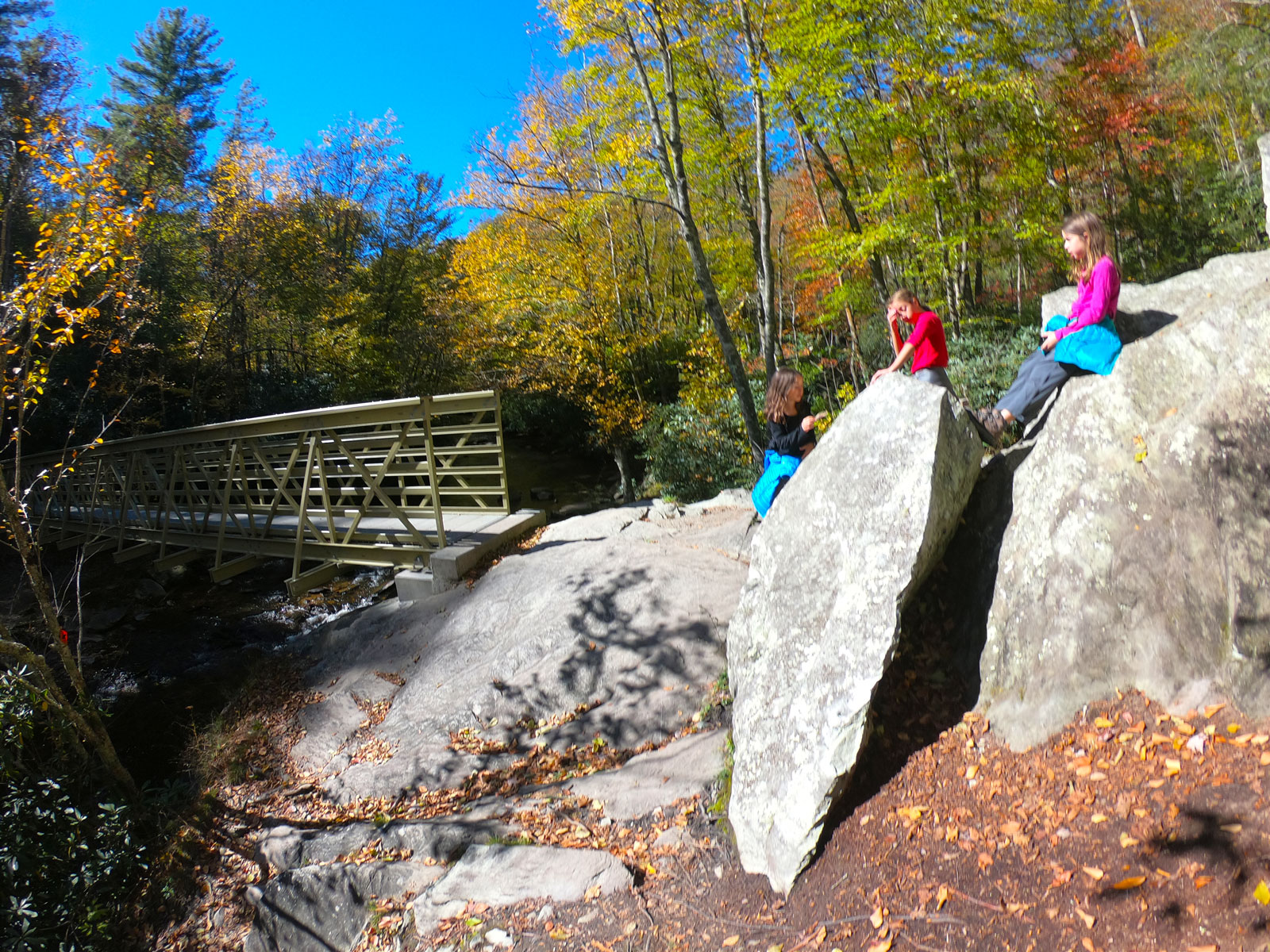 An autumn image of three girls resting on boulders overlooking a bridge over a stream on the Boone Fork Trail near Julian Price Campground on the Blue Ridge Parkway, NC