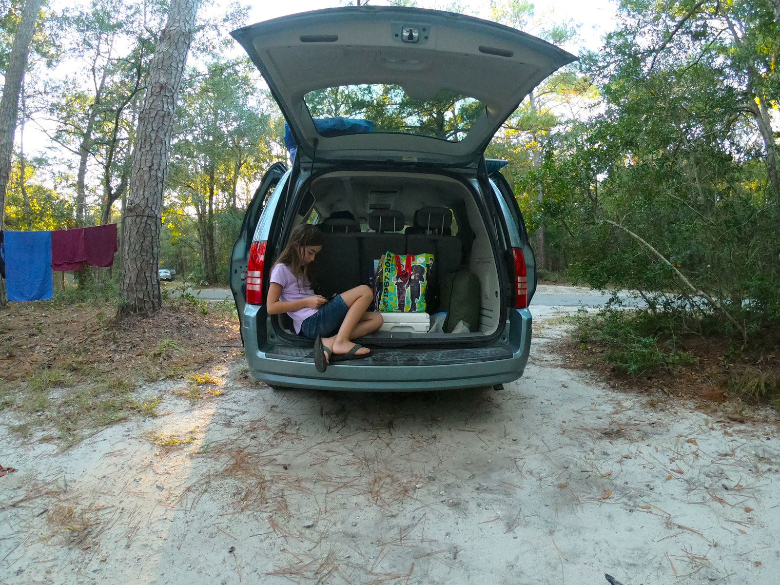 Girl reading in the hatch of a van at Carolina Beach State Park Campground