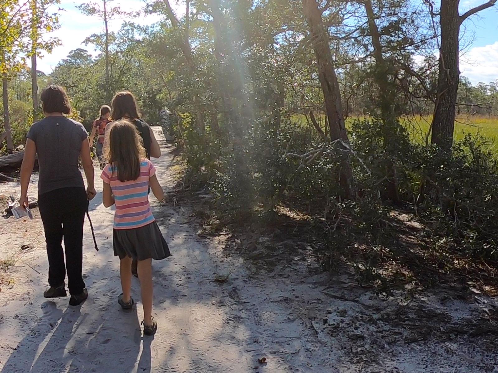 Family walks along a trail at Carolina Beach State Park in North Carolina