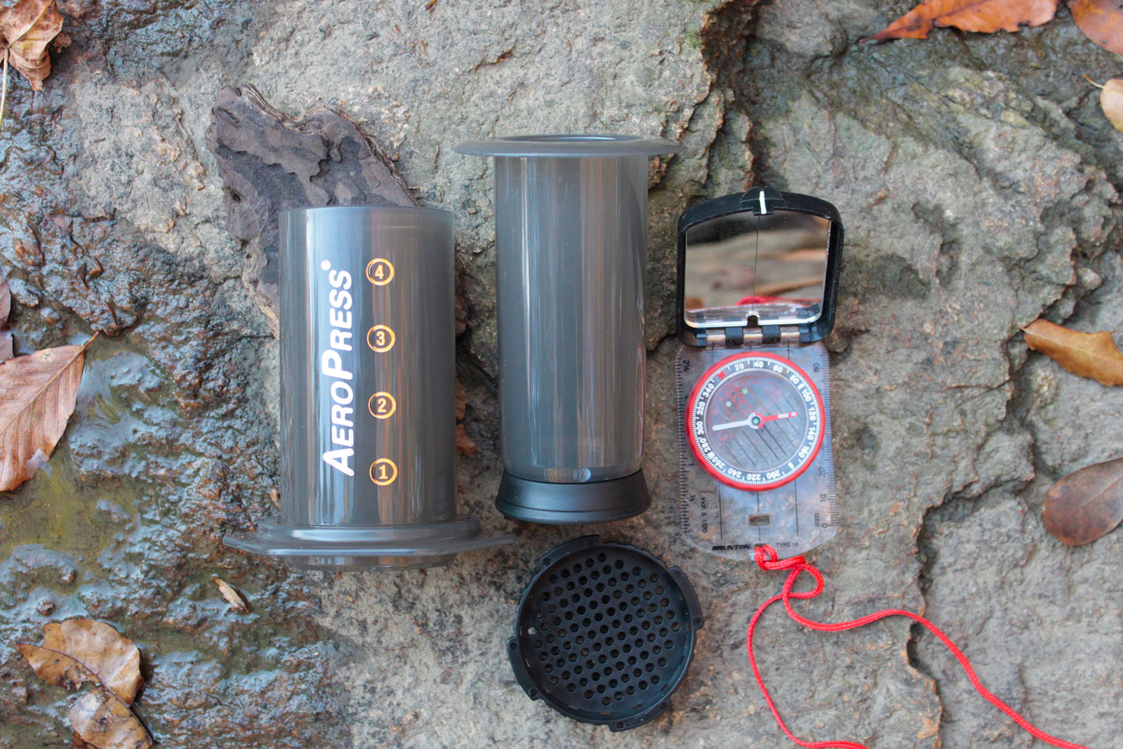 Photograph of an AeroPress Coffee Press on a rock with a compass shown for size