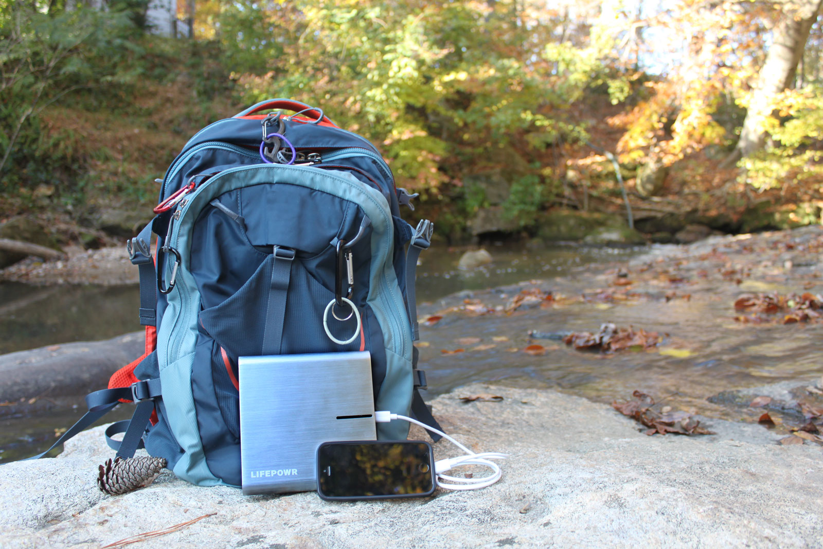 Image of Lifepowr A3 mobile power supply in front of a backpack and camp by a river.