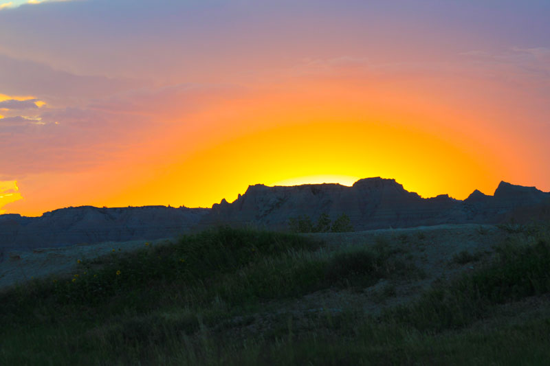 Cedar Pass Campground sunset image with golden-orange sun setting behind butte in Badlands National Park, South Dakota