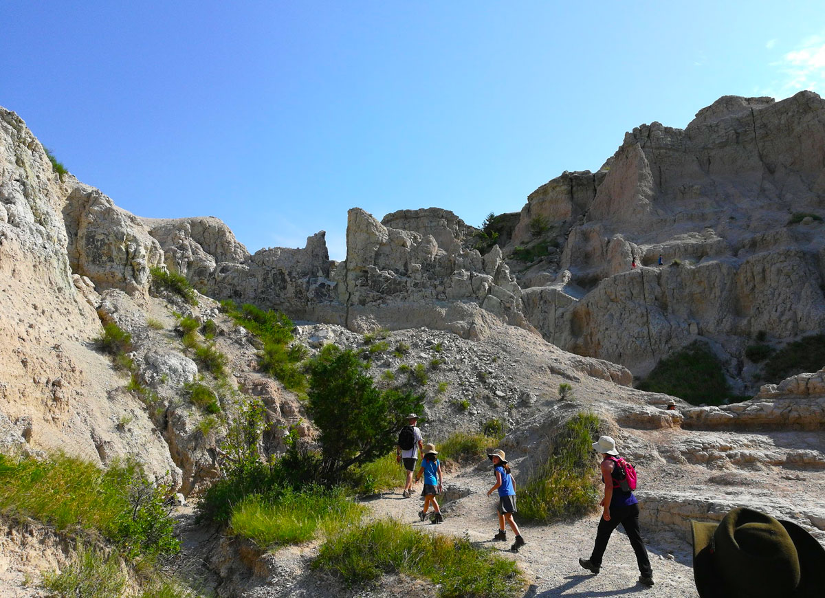 South Dakota Badlands National Park blue sky image of father and three daughters hiking Notch Trail through dusty, rocky geologic formations