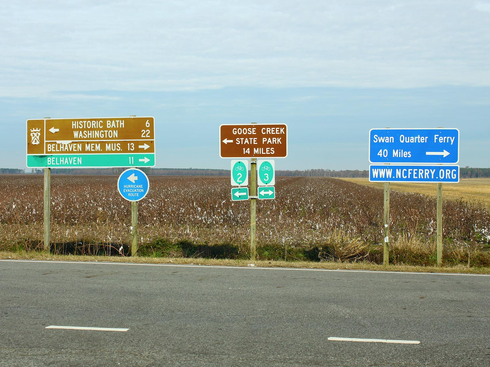 Road signs leaving Bayview ferry station to Goose Creek State Park with cotton field background