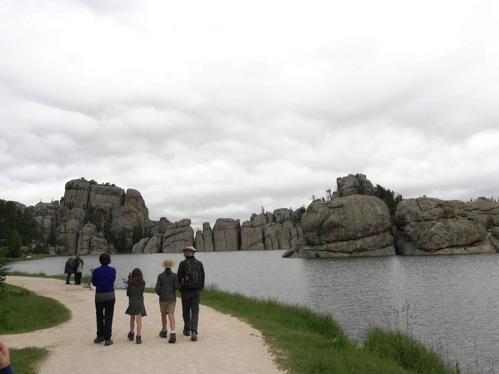 Photo of Sylvan Lake Trail with four people hiking on a cloudy day in Custer State Park, South Dakota