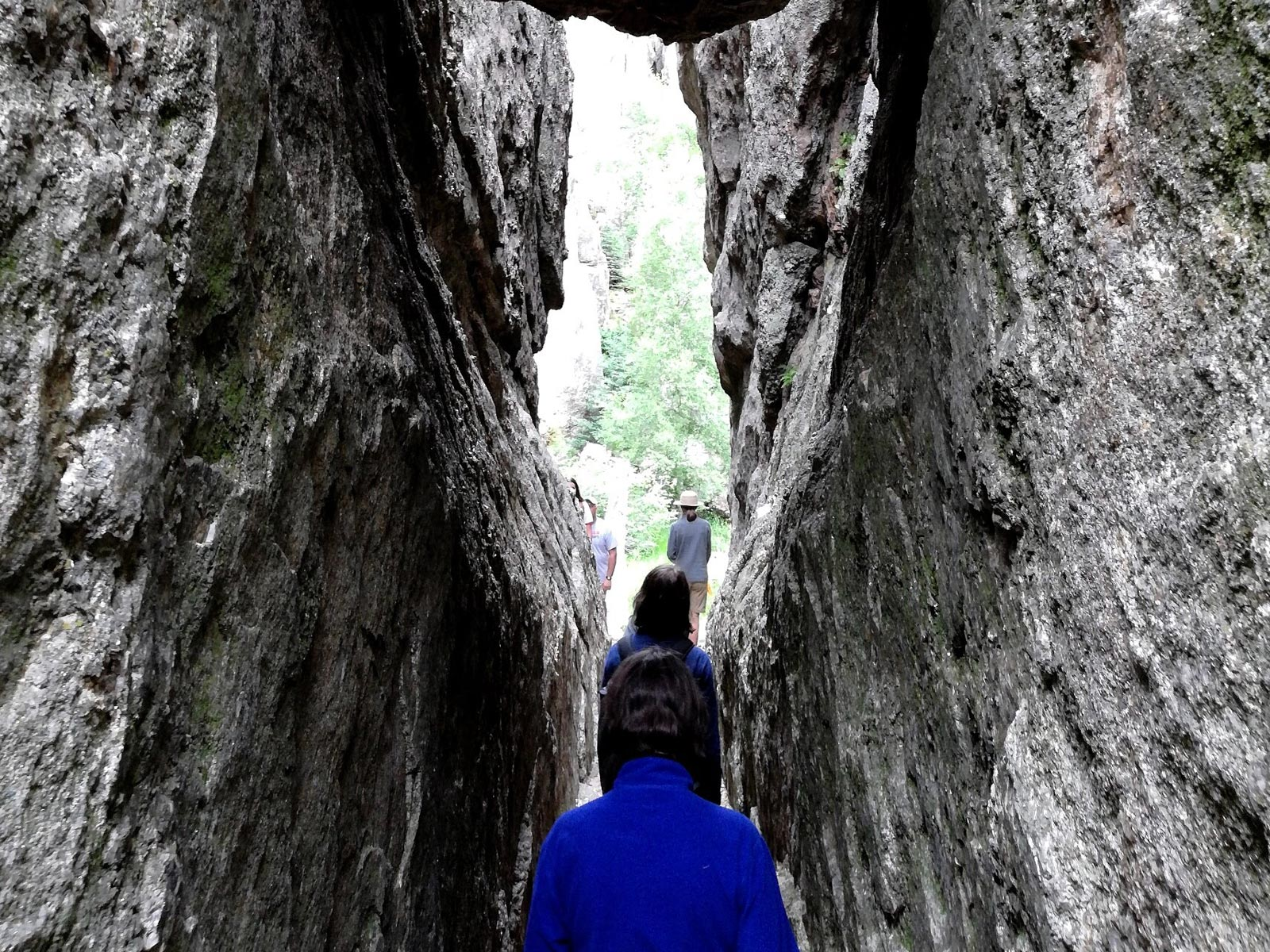Hikers walking through narrow stone crevice on the Sunday Gulch Trail in Custer State Park, South Dakota