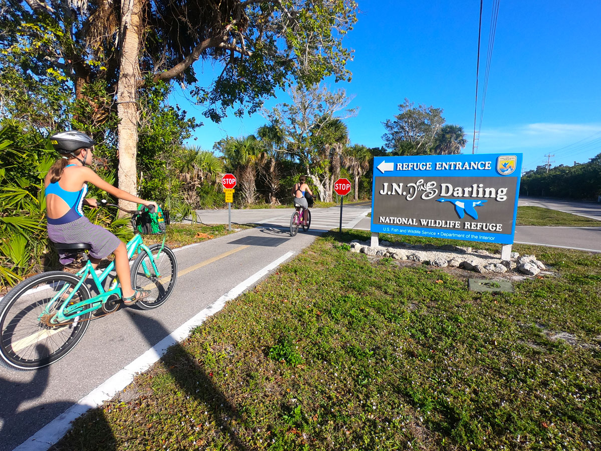 Two teen girls riding bikes in front of J.N.Ding Darling National Wildlife Refuge signage on Sanibel Island, FL