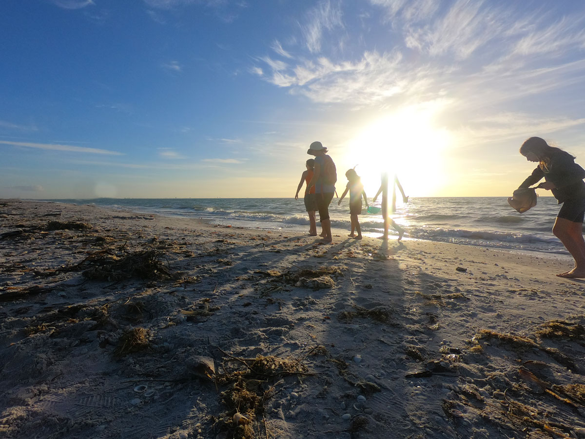 Mother and four daughters looking for seashells at sunset on Sanibel Island, Florida
