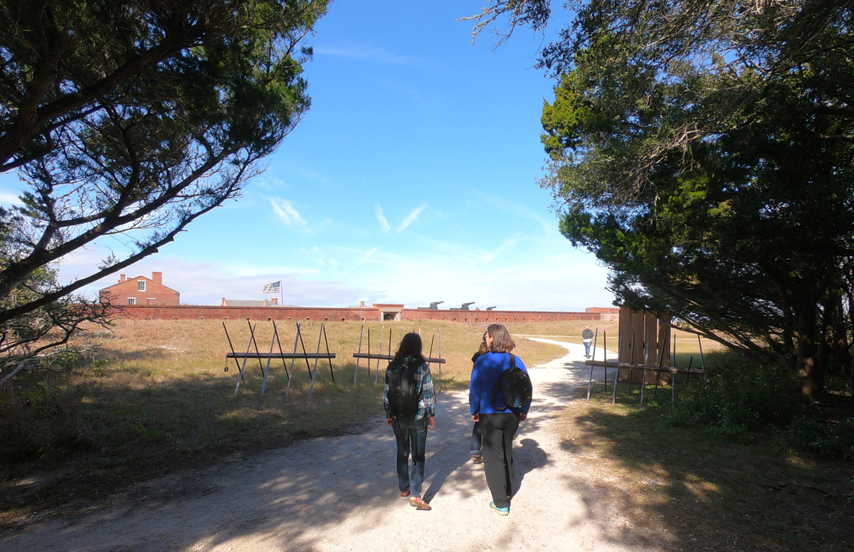 Three people walking toward the entrance to historic Fort Clinch State Park, Florida, on Amelia Island