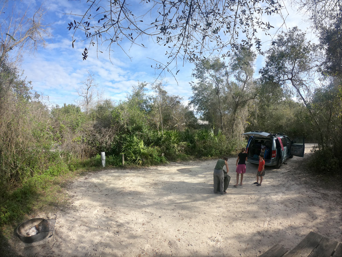 Three people setting up tent at campsite at  Blue Spring State Park, Florida