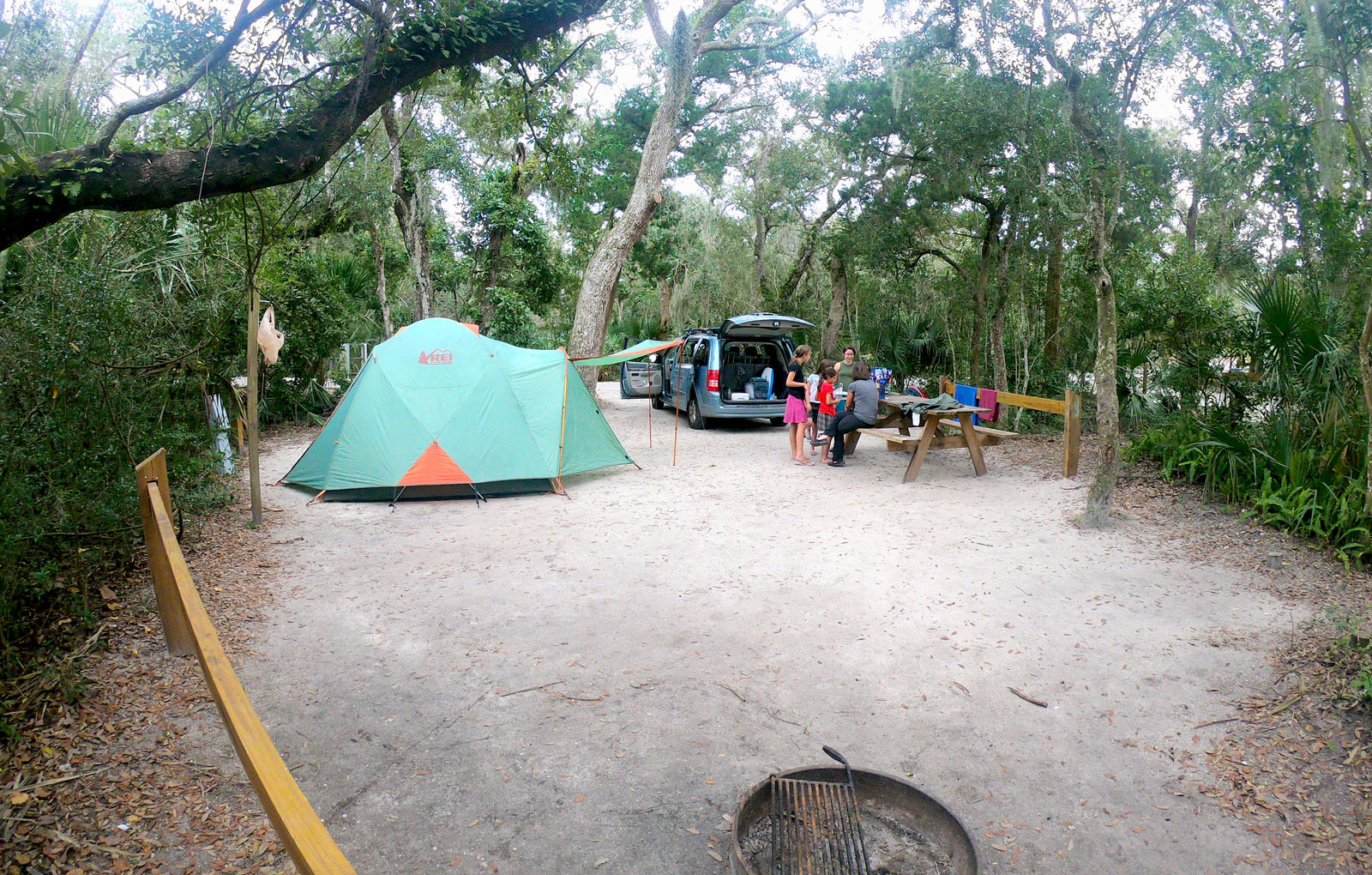 Green REI tent camping set up with van and family in spacious campsite in Anastasia State Park, Florida under canopy of trees near Saint Augustine, Florida