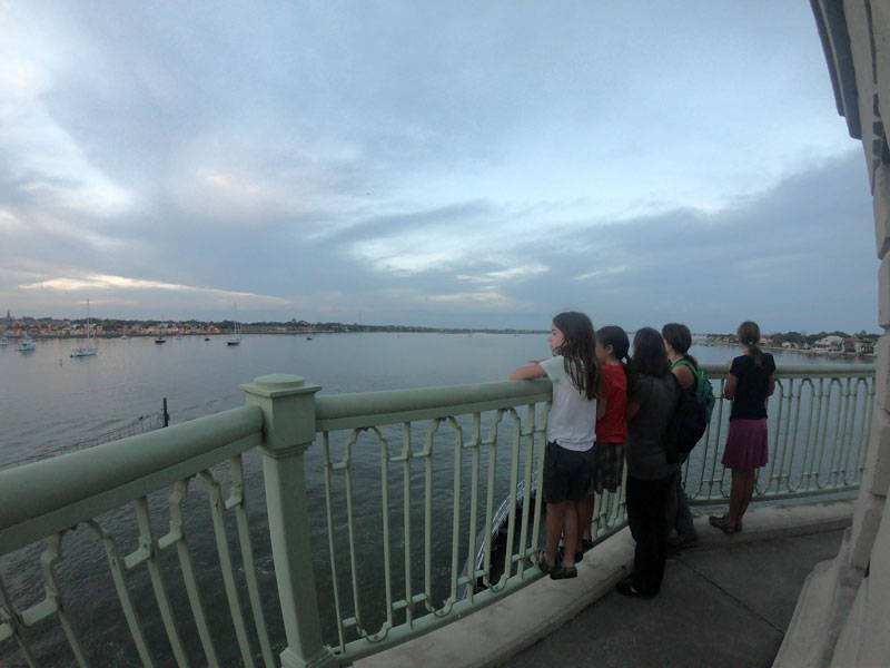 Five people leaning on railing watching the boats in the Matanzas River near Saint Augustine, Florida