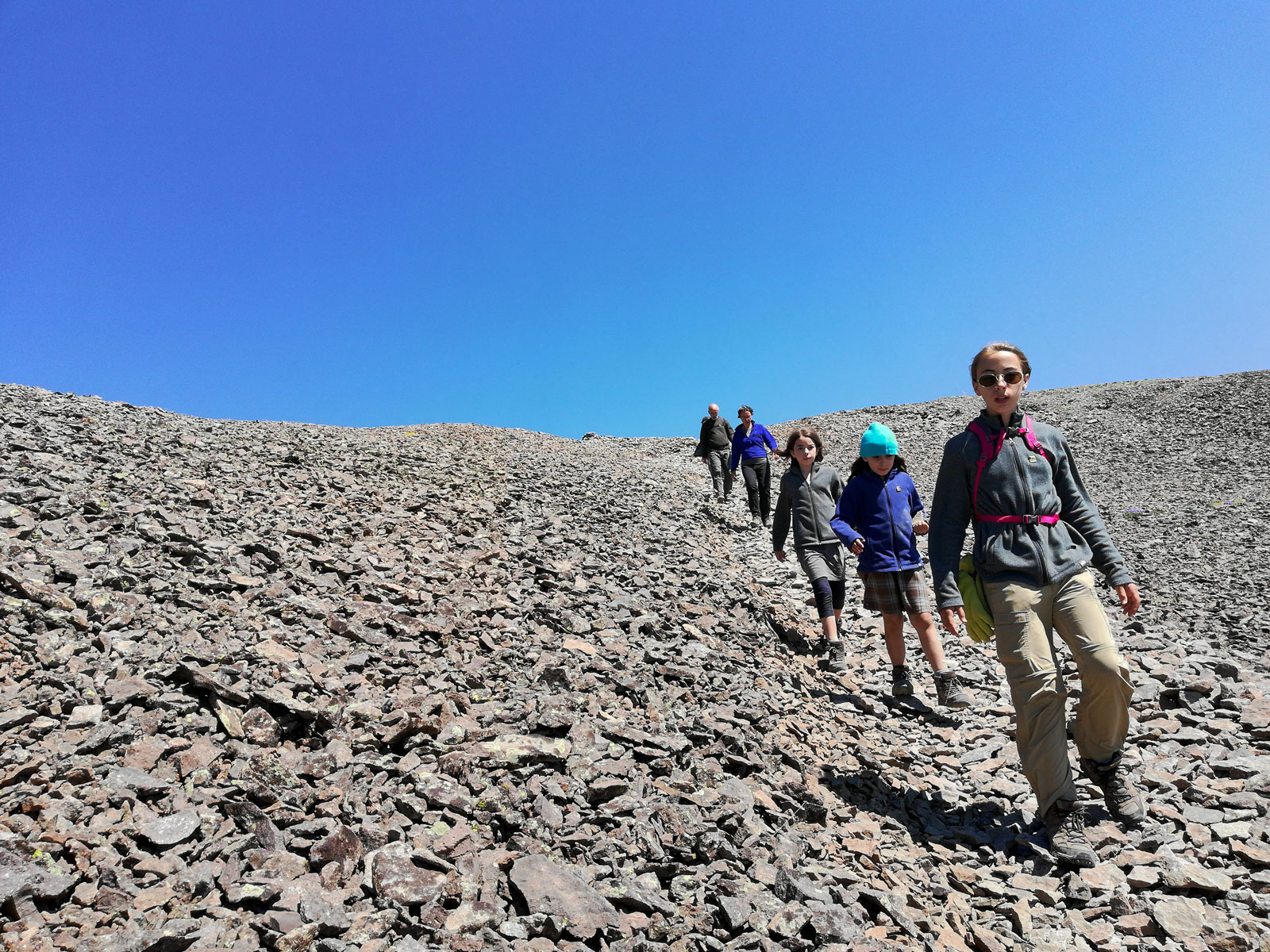 Hikers walking down a scree covered mountainside descending Avalanche Peak in Yellowstone National Park