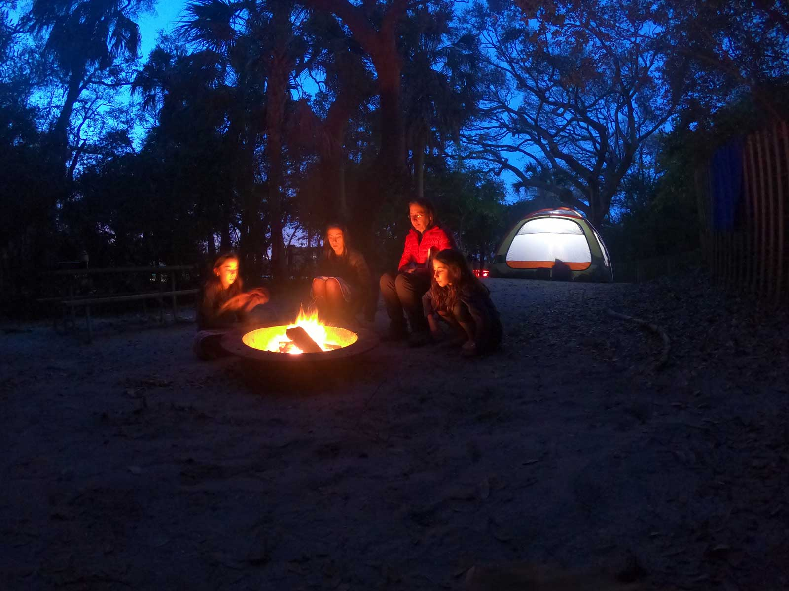 Family gathered around a campfire at night with glowing tent in the background at Edisto Beach State Park, SC