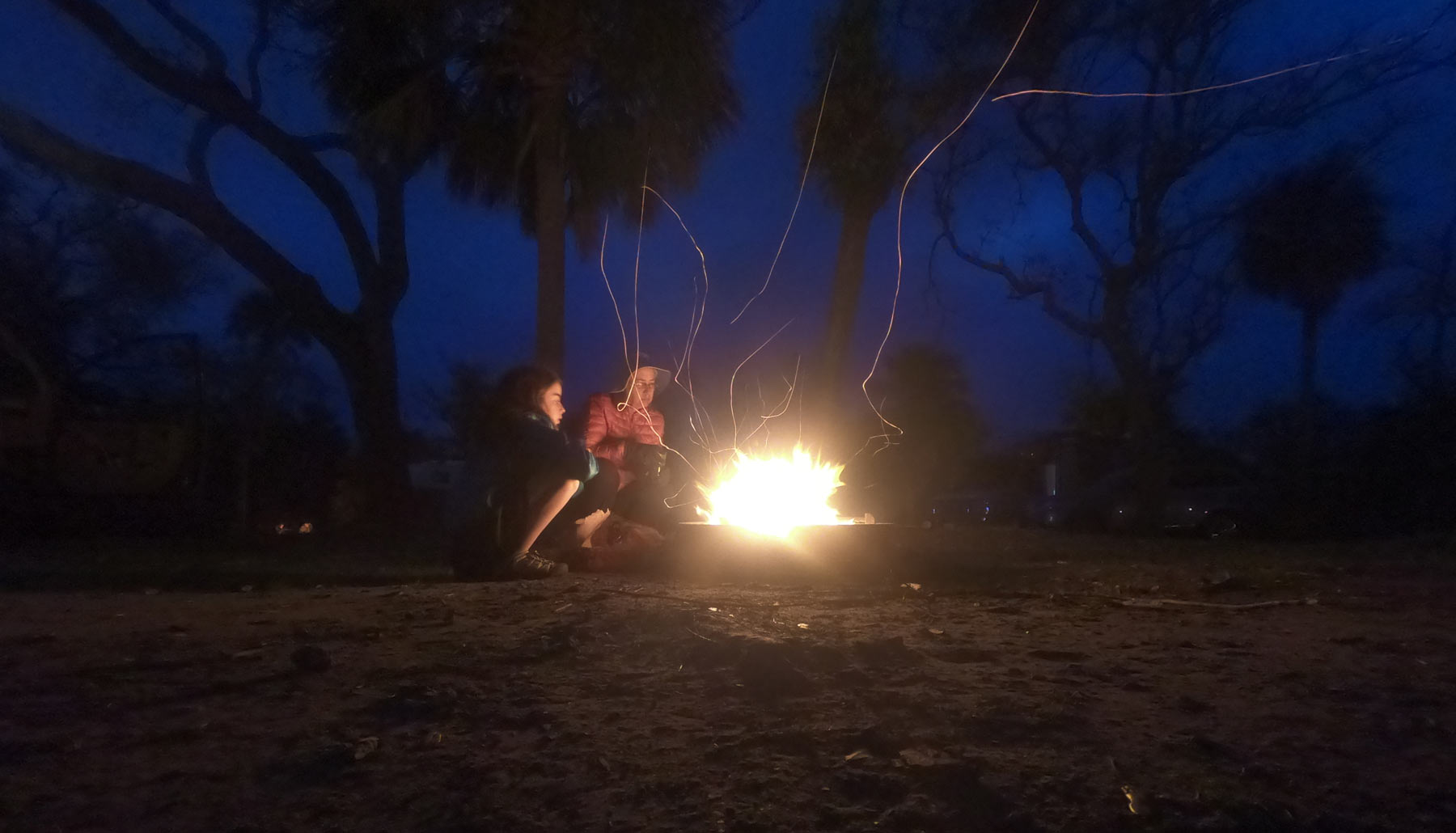 Family gathered around glowing campfire at night