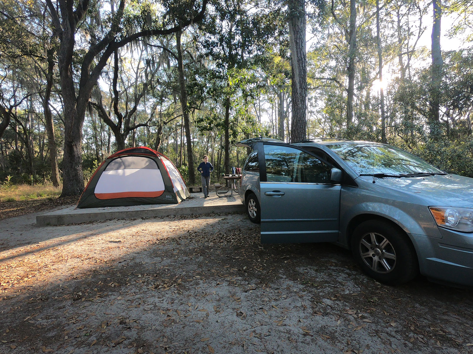 Tent on tentpad, picnic table, and van under pine trees and live oaks at Skidaway Island State Park, Georgia