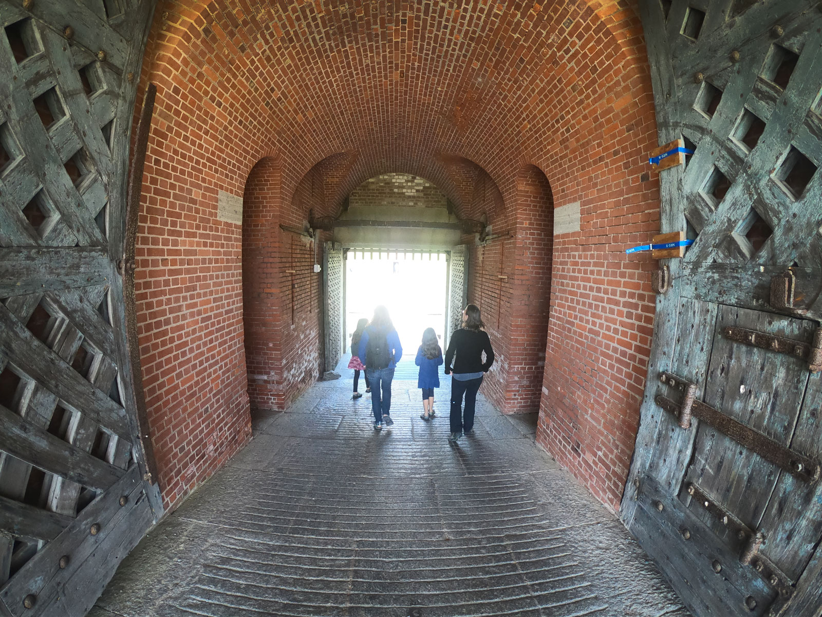 Four people walking through bricked archway entrance to Fort Pulaski National Monument, Georgia
