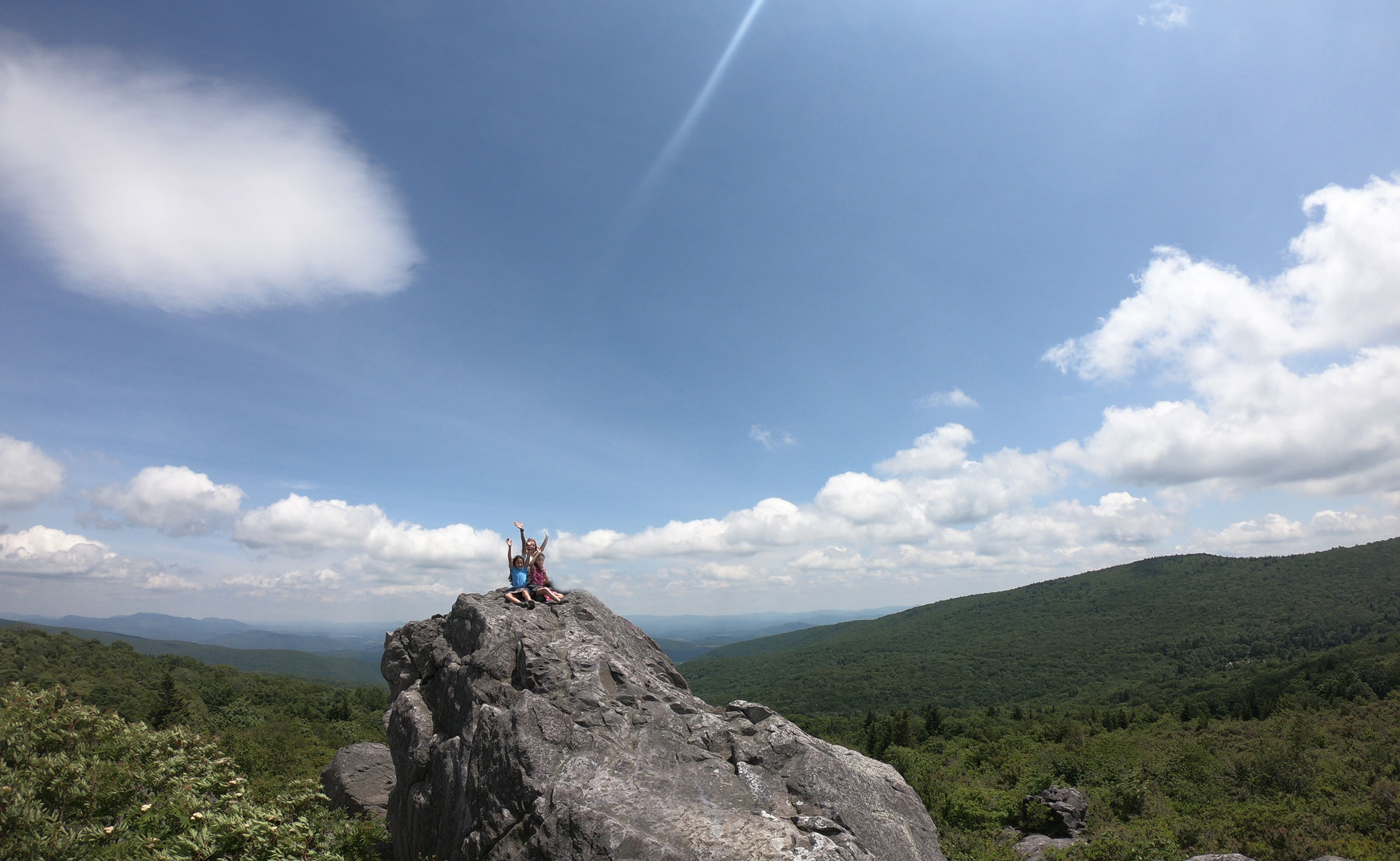 kids raising their hands on the boulder summit while camping and hiking at Grayson Highlands State Park, Virginia