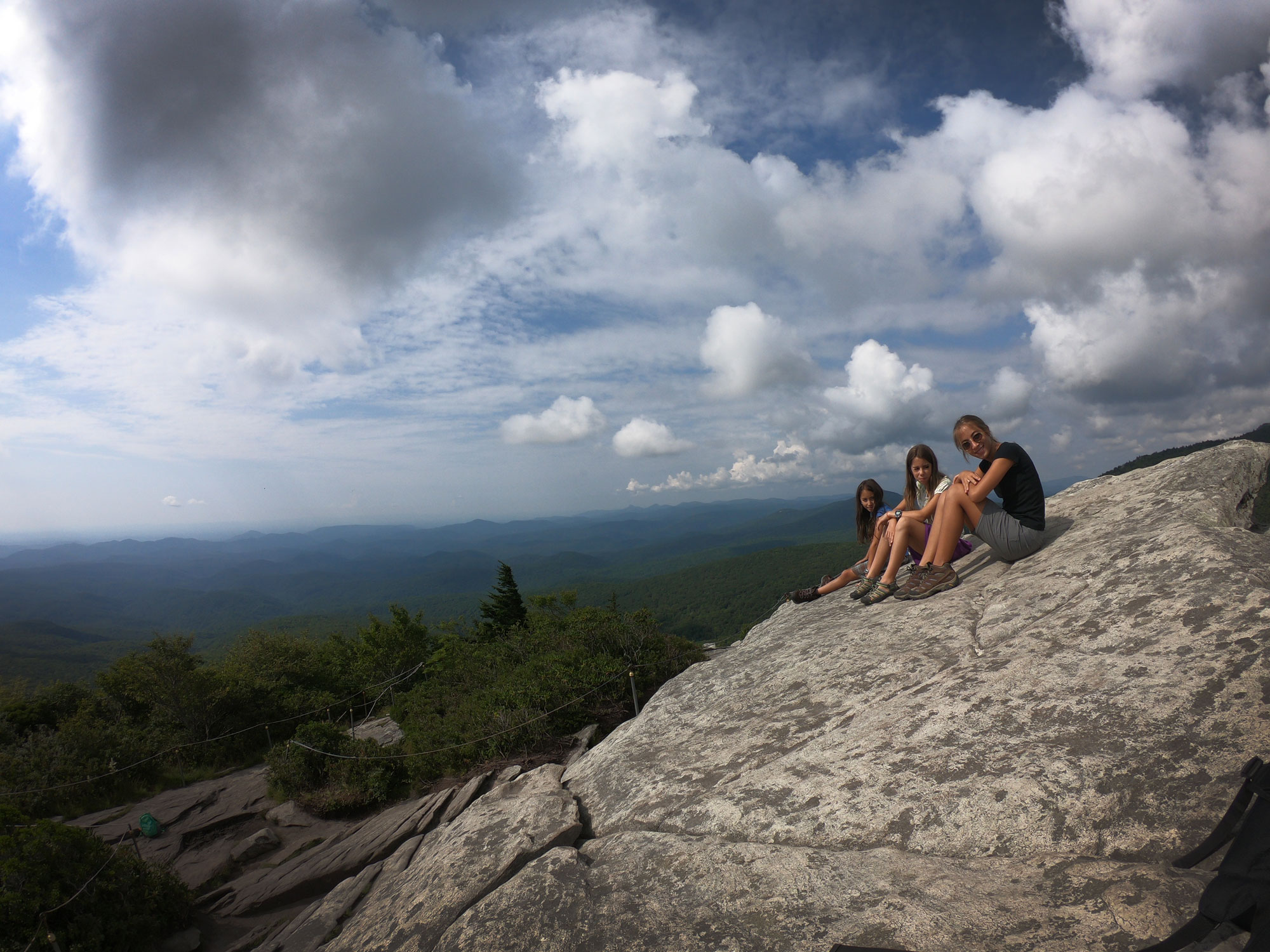 Three kids hiking and sitting at the Rough Ridge summit rocks, off Blue Ridge Parkway, North Carolina