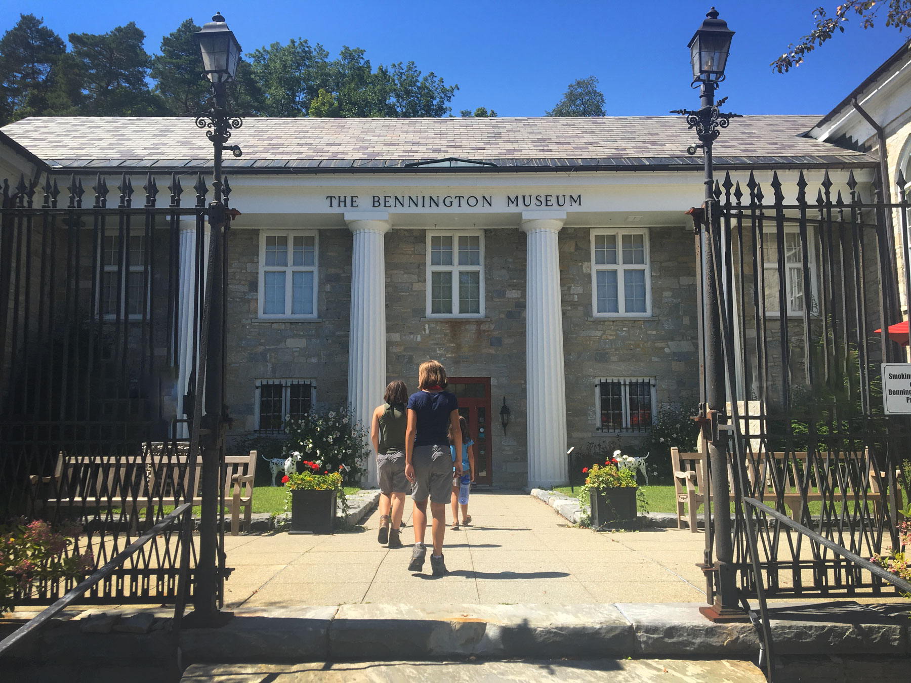 Three kids walking through gates to the Bennington Museum, Vermont