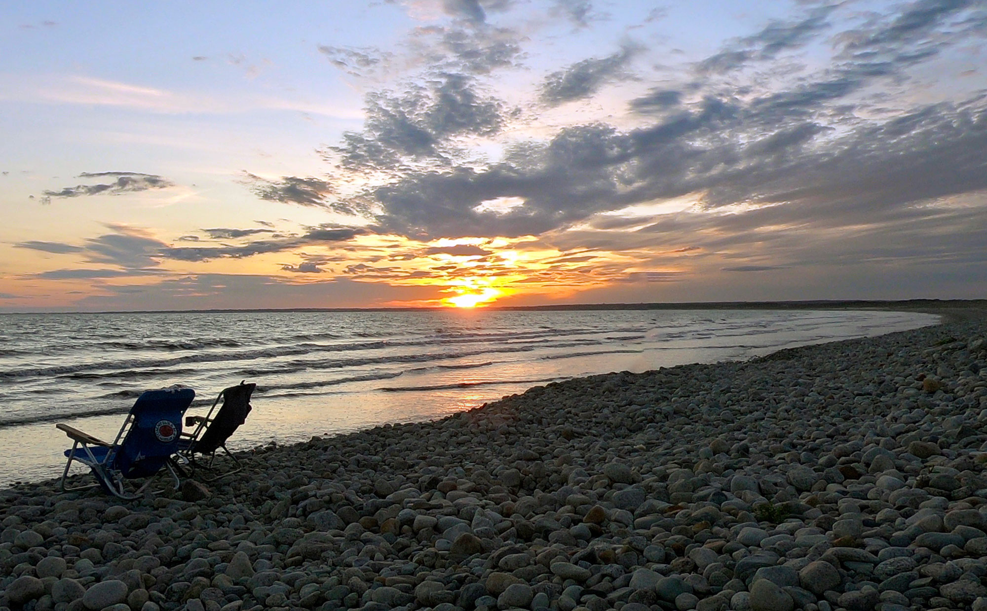 sunset with two beach chairs on the rocky beach while camping at Horseneck Beach State Reservation, Massachusetts
