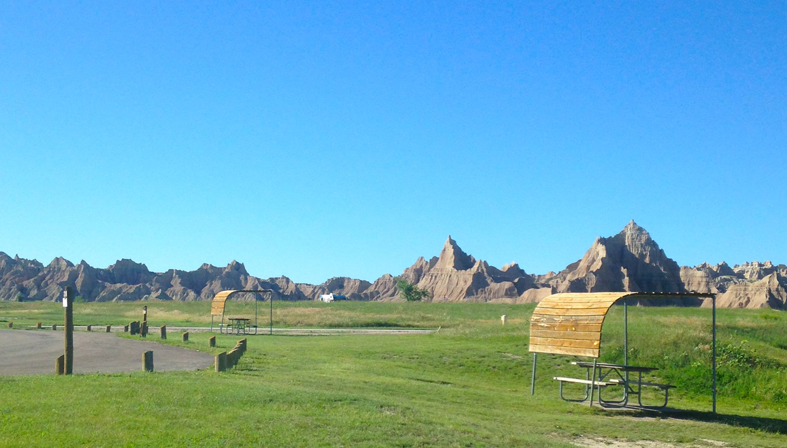 Cedar Pass Campground with covered picnic tables and Badlands National Park as a backdrop