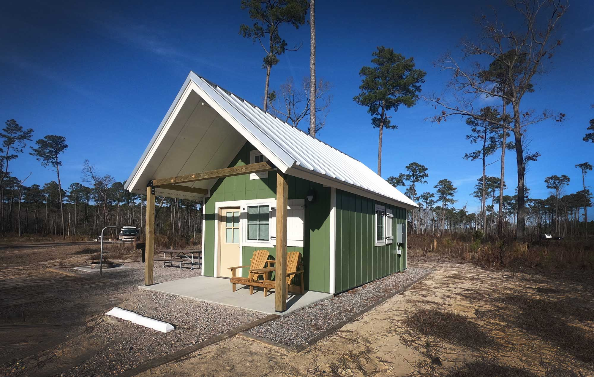 North Carolina's Goose Creek State Park green camping cabin with white metal roof and front porch tAdirondack chairs