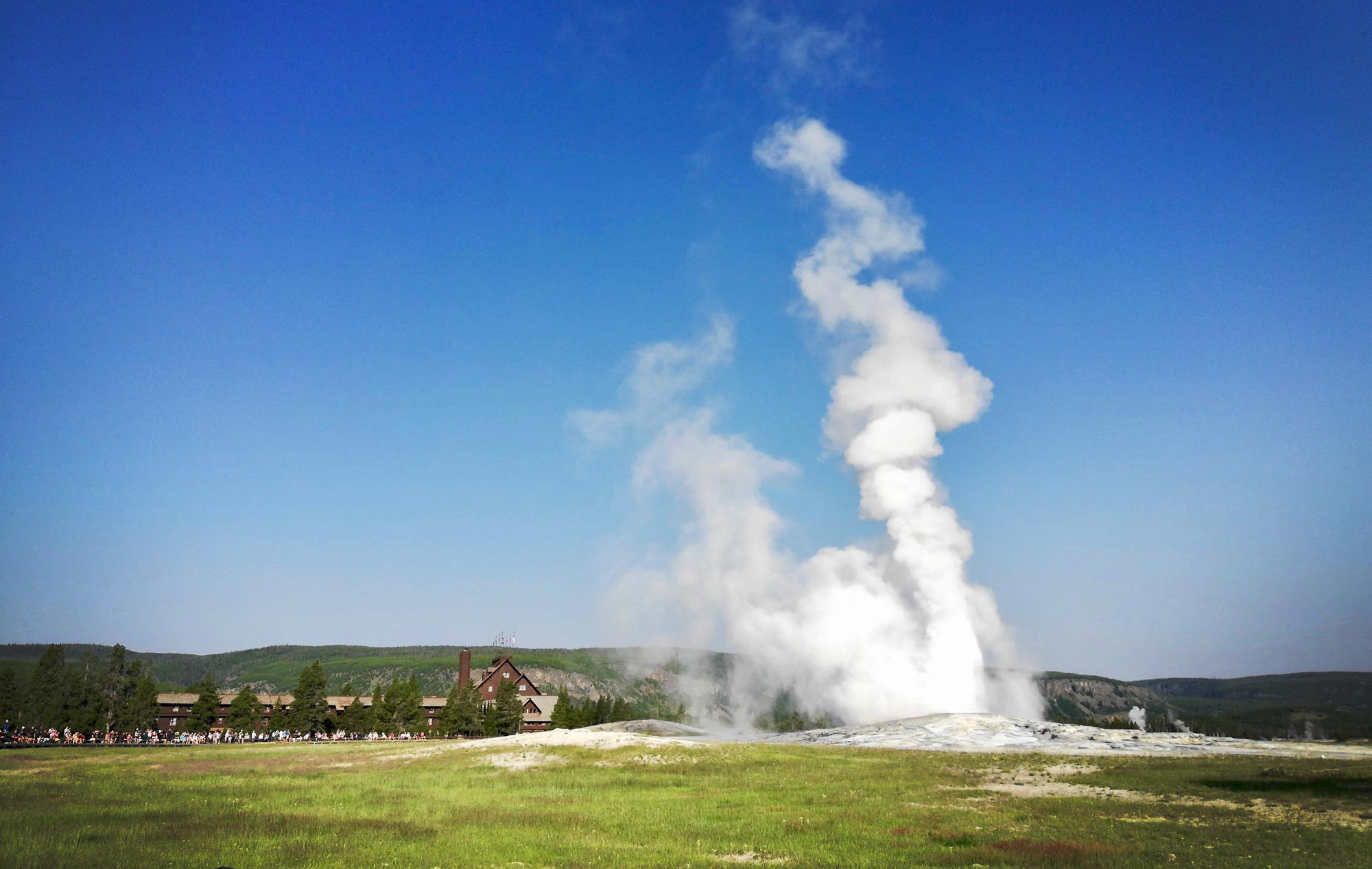Old Faithful Geyser with the Old Faithful Inn in the background in Yellowstone National Park
