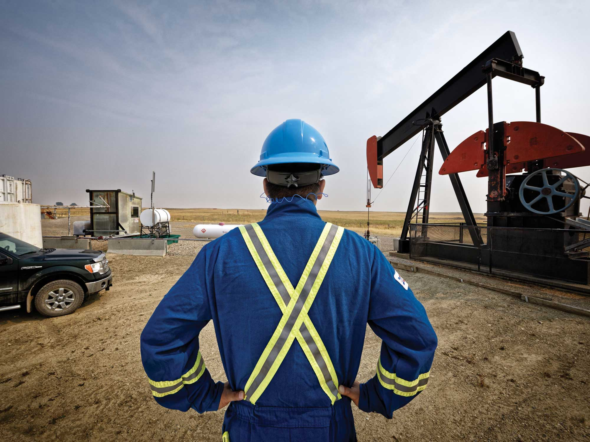 Brand photography for Energy Safety Canada by Jason Stand of a frontline oil and gas worker in front of a pumpjack on a worksite