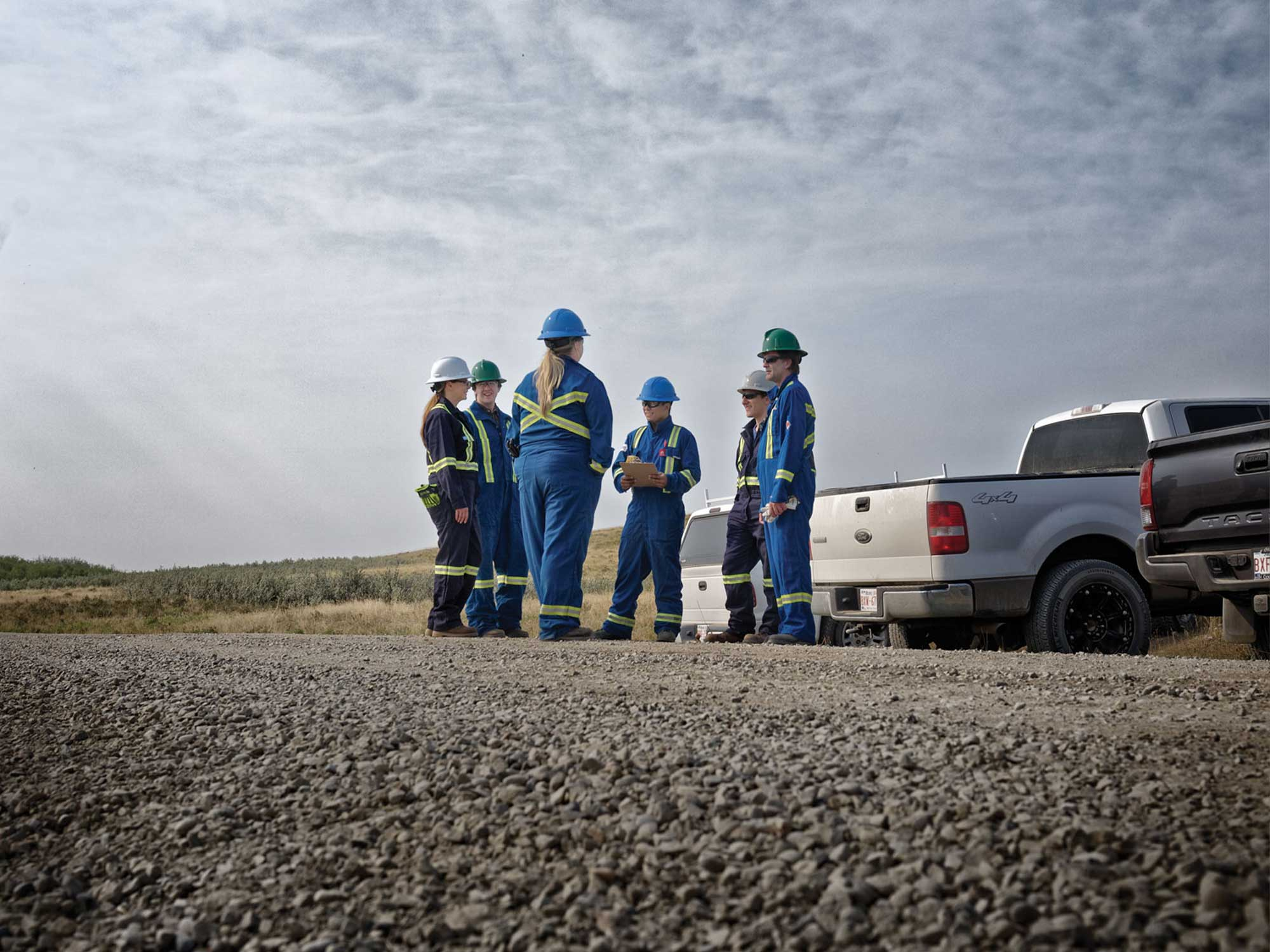 Brand photography for Energy Safety Canada by Jason Stand of a group team of workers in the field having a meeting for studio forum